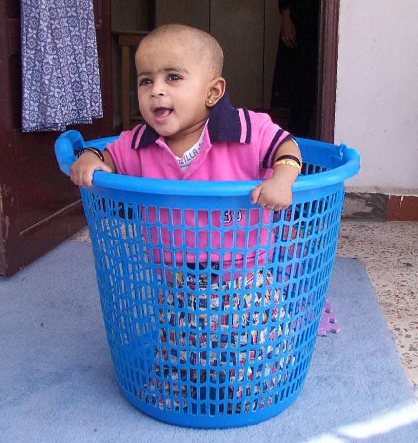child playing in washing basket