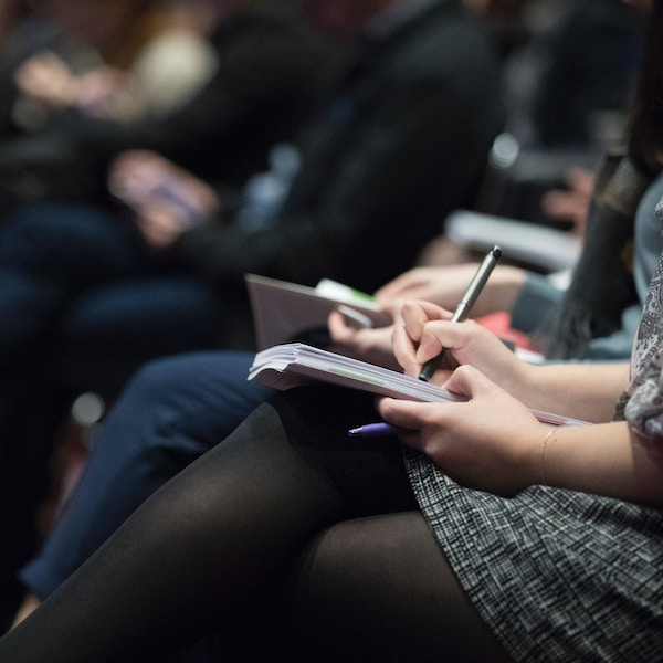 image of conference audience taking notes